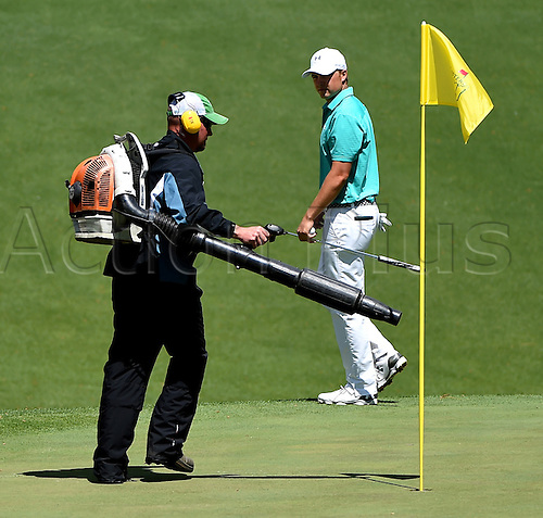 07.04.2016. Augusta, GA, USA. A groundskeeper hurries to blow leaves from the 10th green as Jordan Spieth  monitors progress during the first round of the Masters Golf Tournament on Thursday, April 7, 2016, at Augusta National Golf Club in Augusta, Ga