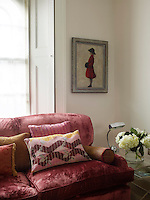 The living room features a pair of red velvet covered sofas filled with comfortable cushions