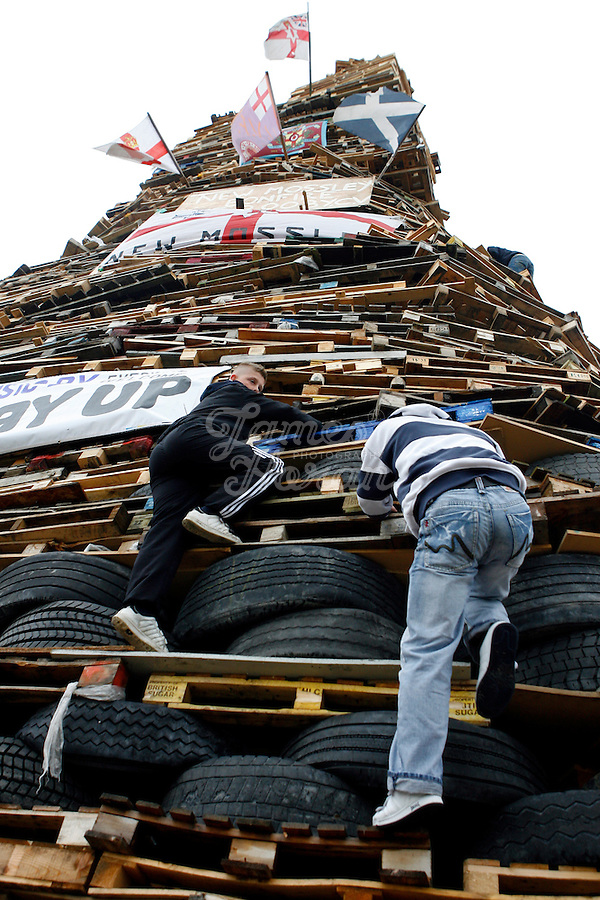 Youths climb down the 30 meter tower of pallets and old tires that will become a giant bonfire on a Loyalist estate of New Mossley, Belfast Northern Ireland.The bonfires which are seen by the Protestant community as a celebration of loyalist culture in the province are lit on the eve of 12 July, which is the anniversary of the Battle of the Boyne at which the Protestant King William of Orange defeated the Catholic King James in 1690. The festival causes outrage in the nearby republician and Catholic areas of the city.