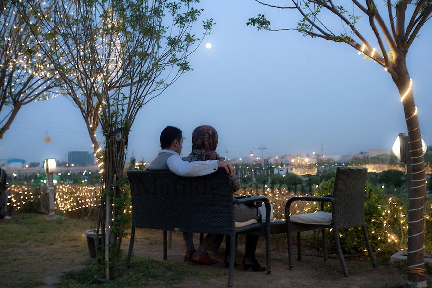 Iraq - Kurdistan - Erbil -   A kurd couple sitting on a bench under the moonlight in Shanadar Park