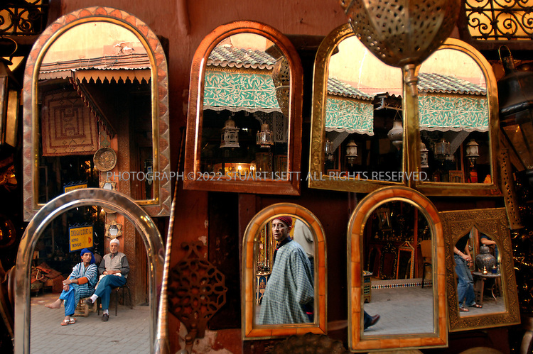 5/8/2006--Marrakesh, Morocco..Pedestrians walk past a mirror and metal wares shop in Marrakesh's ancient Medina district..Photograph By Stuart Isett.All photographs ©2006 Stuart Isett.All rights reserved.