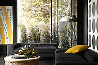 A pair of black modular sofas accessorised with a single yellow cushion furnishes this corner of the open plan living area