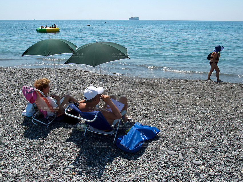Italy. Liguria Province. Genova. Nuovo Lido beach resort. An elderly couple sits under two green umbrellas and is sunbathing while people are swimming in the Mediterranean sea. 17.08.13 © 2013 Didier Ruef