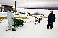 Cim Smyth runs down the street as he leaves Ruby on Saturday morning with the Yukon River in the background during Iditarod 2008