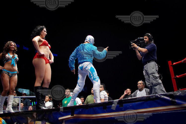 A Luchador (fighter) speaks to the camera before the start of a match, broadcast live on Tuesdays and Fridays. Lucha Libre is a style of wrestling started in Mexico in 1933. The name means Free Fight, and matches tend to be focussed on spectacle and theatre with fans cheering for their favourite characters, who wear masks while jumping from the ropes, flipping opponents, and occasionally crashing into the crowd..