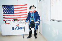 """Anthony Nino stands by the food table at the campaign headquarters of Kentucky senator and Republican presidential candidate Rand Paul in Manchester, New Hampshire. At the time, Paul was visiting the office to greet supporters and call voters. Nino was helping with phonebanking efforts. He said his outfit, which he made himself, is meant to """"give a visual message that our movement is based on the Constitution."""""""
