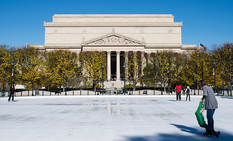 UNITED STATES - NOVEMBER 18: Several midday skaters take advantage of warm temperature to skate at the ice rink at the National Gallery of Art Sculpture Garden with the National Archives in the background on Monday, Nov. 18, 2013. The rink opened for the season on Friday. (Photo By Bill Clark/CQ Roll Call)