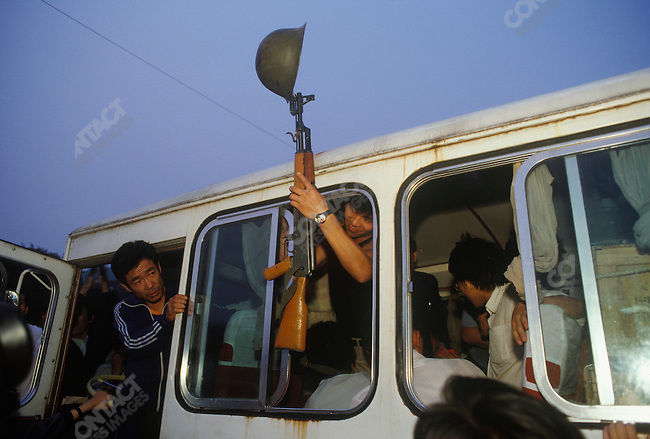 Student demonstrators display guns and flags found on army buses taken over by protesters, before the military crackdown, Changan Avenue, Beijing, China, June 1989