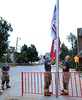 NWA Democrat-Gazette/ANDY SHUPE<br /> Josh Harrison (left) watches as Edward Maria (center) and Marcus Mason, all firefighters with the Fayetteville Fire Department, work together Friday, Sept. 11, 2015, to raise the U.S. and Arkansas flags to half staff outside the department's Station One in Fayetteville. The U.S. flag that bears the names of victims of the Sept. 11, 2001 terrorist attacks and was flown at half staff on the 14th anniversary of the attacks.