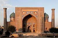 "View from the front of the Sher-Dor Madrasah, 1619-36, Registan, Samarkand, Uzbekistan, pictured on July 15, 2010 at sunset which lights up the elaborately tiled facade and domes. The Sher-Dor Madrasah, commissioned by Yalangtush Bakhodur as part of the Registan ensemble, and designed by Abdujabor, takes its name, ""Having Tigers"", from the double mosaic (restored in the 20th century) on the tympans of the portal arch showing suns and tigers attacking deer. Samarkand, a city on the Silk Road, founded as Afrosiab in the 7th century BC, is a meeting point for the world's cultures. Its most important development was in the Timurid period, 14th to 15th centuries. Picture by Manuel Cohen."