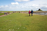 Tourists walking to the castle, Holy Island, Lindisfarne, Northumberland, England, UK