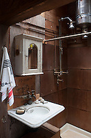 A rustic indoor shower is serviced by a small water geyser and a marble wash basin