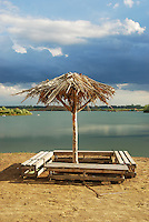 Alone standing parasol (umbrella) on abandoned beach