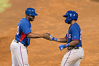 AZL Rangers first base coach Jeremy Moore (43) congratulates Stanley Martinez (29) after reaching base during an Arizona League playoff game against the AZL Indians 1 at Goodyear Ballpark on August 28, 2018 in Goodyear, Arizona. The AZL Rangers defeated the AZL Indians 1 7-4. (Zachary Lucy/Four Seam Images)