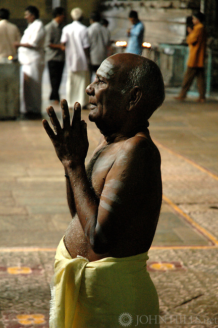 South India - A man about to enter retirement offers pranams at the Meenakshi Shiva temple in Madurai, the cultural capital of Tamil Nadu. Eighty percent of Indians are Hindus who believe worshiping at the temple brings blessings and good fortune.