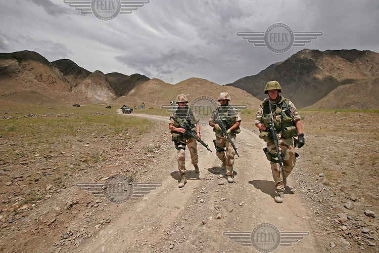 Norwegian ISAF soldiers walk a road in the mountains  some distance from Kabul