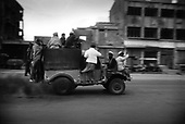 Kabul, Afghanistan<br /> November 2001<br /> <br /> Several men pile onto a truck to travel down a main road in the city.