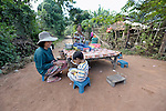 Women--and a small boy--eat a morning meal at a restaurant along the roadside in the Cambodian village of Talom.