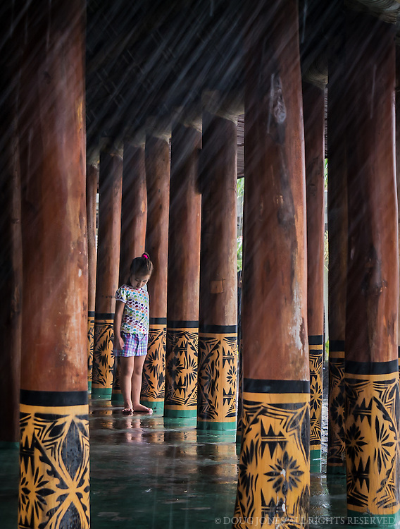 "My wife and I were waiting for an inter-island flight from Pago Pago, in American Samoa, to Apia, in Western Samoa.  Our flight was delayed over an hour due to a major rainstorm affecting both islands.  Totally bored, I kept watching this young Samoan girl playing with her siblings in this large, open structure, supported by this individually carved posts.  I finally grabbed my camera and started photographing the posts and the reflection of the water on the green, painted floor.  After 4-5 shots, the girl ran into the frame, put her hands to her side, and stopped in her tracks as if to gesture, ""Just a moment..."""