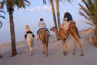 Family riding three camels in desert, Douz, Tunisia