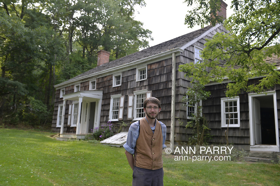 Old Bethpage, New York, USA. 30th August, 2015. Matt, a seasonal worker wearing traditional style American clothing, stands at the front of the Powell House after giving a tour during the Old Time Music Weekend at Old Bethpage Village Restoration. The wood shingled house was built in 1750 and is restored to its expanded 1855 size, and is the only building standing on its original location in the village.