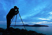 Landscape photographer at work on the Pembrokeshire coast near St David's, Wales