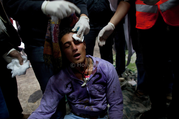Medics put pressure on a young man's brow where he was hit by bird shot, at the field hospital in Tahrir Square, Cairo, Egypt, Sunday, Nov. 20, 2011. Around 1500 people have been injured and 23 killed in the clashes ahead of Egypt's parliamentary election beginning on November 28.