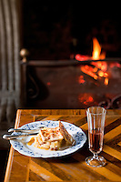 Detail of a dessert of apple strudel served with a glass of sweet wine in front of a roaring fire
