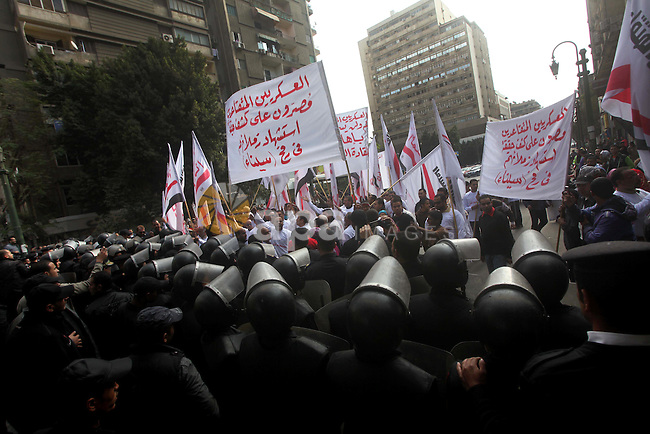 protesters holding signs,  in front of police officers near the Shura Council, the upper house of parliament where the Constituent Assembly drafted the country's new constitution, as protesters against Egypt's President Mohamed Morsi chant slogans in front of them, while Morsi gives a speech before a newly empowered senate in Cairo on December 29, 2012. Morsi said in the address, a disputed new constitution guaranteed equality for all Egyptians, and downplayed the country's economic woes. Photo by Ashraf Amra
