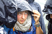 "Italian girl trying to find cover under heavy rain during the ""Be A lighthouse"" -ceremony.  Photo: Mikko Roininen / Scouterna"
