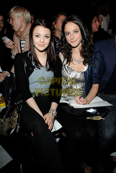 KATHERINE PRESCOTT & KAYA SCODELARIO.At the PPQ Fashion Show during London Fashion Week - Day 2 , BFC Show Space, Somerset House, London, England, UK, February 20th 2010..LFW  length sitting blue leather jacket black leggings half 3/4 grey gray cardigan jeans .CAP/CAN.©Can Nguyen/Capital Pictures