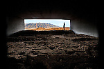 landscape mountains framed by dirt and concrete enclosure with silhouette of man in profile conceptualizes the interface of man and the environment.  taken on interstate highway near bernalillo, new mexico.  horizontal composition with copy space.