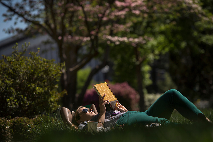 UNITED STATES - APRIL 18: A Hill staffer reads a book during the lunch hour on the East Lawn of the Capitol, April 18, 2017. (Photo By Tom Williams/CQ Roll Call)