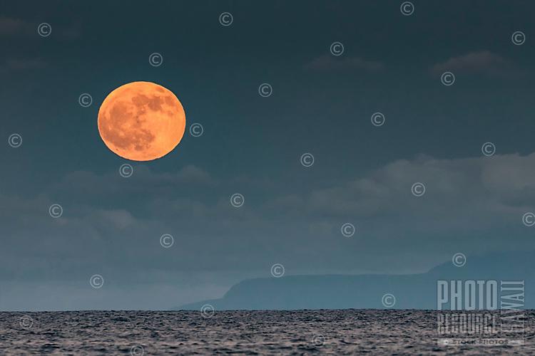 The full moon rises through the vog over Moloka'i, seen from Makapu'u, Hawai'i Kai, East O'ahu.