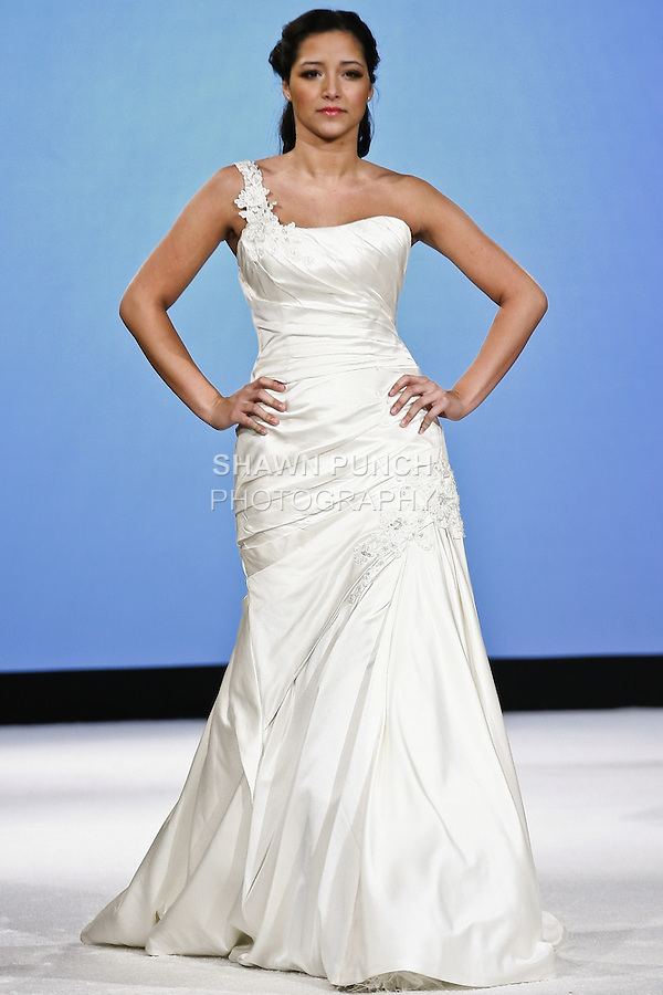 Model walks the runway in B023 by Casablanca Bridal. Duchesse silk satin gown with Swarovski Crystals and crystal wequins, pearls, and beaded flower appliques. Neckline has one sholder strap, and bodice is ruched going into fit and flare silhouett. During the Wedding Trendspot Press Fashion Show at the Waldorf-Astoria; October 18 2009