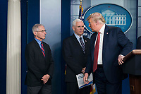 United States President Donald J. Trump, right, delivers remarks on the COVID-19 (Coronavirus) pandemic alongside members of the Coronavirus Task Force in the Brady Press Briefing Room at the White House in Washington, DC, March 25, 2020, in Washington, D.C.  At left is Director of the National Institute of Allergy and Infectious Diseases at the National Institutes of Health Dr. Anthony Fauci and at center is US Vice President Mike Pence.<br /> Credit: Sarah Silbiger / Pool via CNP/AdMedia