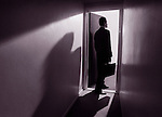 Businessman entering a light filled room.
