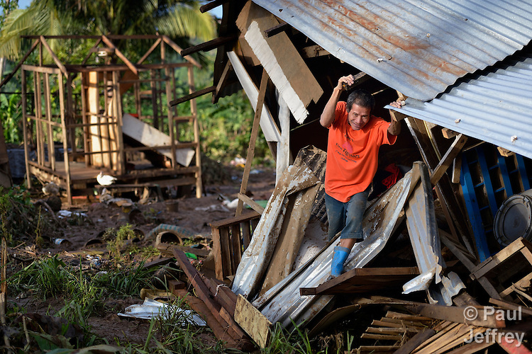 In the wake of Typhoon Bopha's passage through the southern Philippines island of Mindanao, Armando Guniyon climbs through the rubble of his home, damaged by flood waters, in Cagayan de Oro.