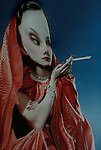 A woman wearing a red dress smoking a long cigarette