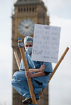 09/10/2011. LONDON, UK. A protester dressed in surgical scrubs sits on a bamboo tripod holding a placard.  Hundreds of protesters today (Sunday) blocked Westminster Bridge as they protested against cuts to the British National Health Service (NHS). Photo credit: Matt Cetti-Roberts