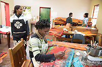 Africa, Malkerns, Swaziland, Nest organization artisans project. Nest is partnering with Baobab Batik & local artisans to help market their batik products to global markets and better sustain their local community. Women waxing batik at Baobab batik.