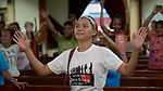 Methche Bayan raises her arms as she sings during worship at Knox United Methodist Church in Manila, Philippines. The service is part of a weekday program where the church opens up to poor people in the neighborhood, offering showers, food, fellowship, and an opportunity to worship together.