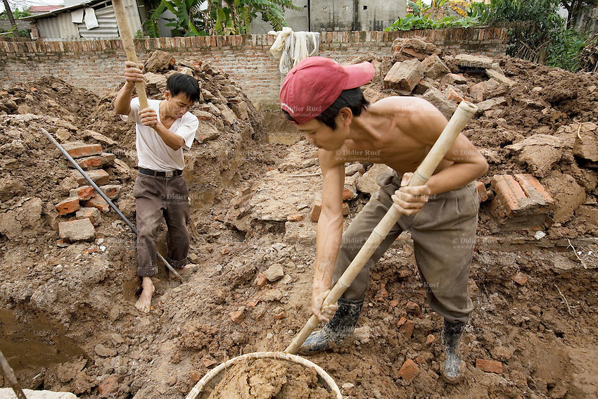 Vietnam. Ha Tay province. Lai Xa. Building site. Destruction of old traditional house and modern new house under construction. Two blue-collar manual workers with pickaxe and bamboo stick in hands. One man is stripped to the waist and wears a baseball cap on his head. Lai Xa is a typical hamlet (village) of the Red River delta region and is part of the Kim Chung commune located 15 km west of Hanoi. The peri-urban location is under increasing pressure of urbanization. 06.04.09 © 2009 Didier Ruef