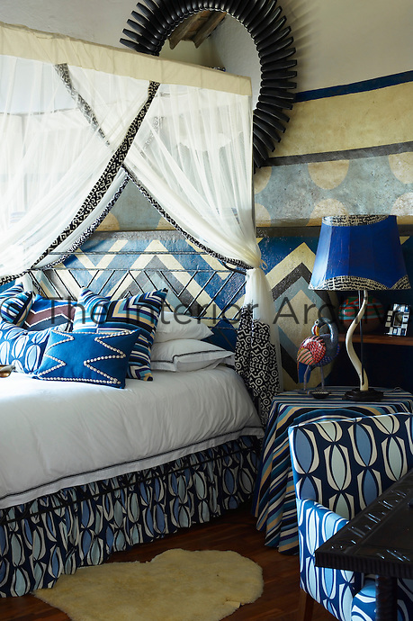 A bedroom at Singita Pamushana Lodge, Malilongwe Trust, Zimbabwe, furnished in colourful blue tribal patterns and a four poster bed