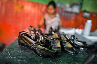 Newly made pairs of women's patent leather shoes are seen placed on the table in a shoe making workshop in San Salvador, El Salvador, 16 November 2016.