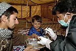 "Following an October 8, 2005, earthquake in northern Pakistan, members of Action by Churches Together in Pakistan, including Church World Service and the Church of Pakistan, responded quickly to the needs of thousands of affected families. Here a physician from Peshawar, Hizkial Barkat (right), a member of a CWS-supported delegation from the Peshawar diocese of the Church of Pakistan, attends to injured patients at a CWS-sponsored ""tent city"" near Balakot."