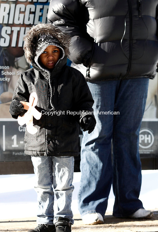 Waterbury, CT- 22 January 2014-012214CM02-  Anthony Barham, 4, of Waterbury keeps warm as he waits for a bus with his cousin, Tunisia Edmonds, on the Waterbury Green Wednesday afternoon.  According to the National Weather Service, the cold is expected to continue Thursday with a high near 21.  Christopher Massa Republican-American
