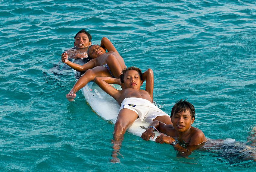 Kuna Indian boys on a surfboard in the water off Corbisky Island, San Blas Islands (Kuna Yala), Caribbean Sea, Panama