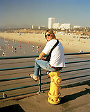 USA, California, Santa Monica, Los Angeles, a young man sits on a fire hydrant on the Santa Monica Pier with Santa Monica State Beach in the distance