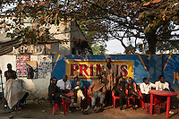 "KINSHASA, DEMOCRATIC REPUBLIC OF CONGO - July 16: Sapeurs from the group Leopard de la Sape relaxes at an outside bar show on July 16, 2014, in Kinshasa, DRC. The word Sapeur comes from SAPE, a French acronym for Société des Ambianceurs et Persons Élégants or Society of Revellers and Elegant People and it also means, to dress with elegance and style"". Most of the young Sapeurs are unemployed, poor and live in harsh conditions in Kinshasa, a city of about 10 million people. For many of them being a Sapeur means they can escape their daily struggles and dress like fashionable Europeans. Many hustle to build up their expensive collections. Most Sapeurs could never afford to visit Paris, and usually relatives send or bring clothes back to Kinshasa. (Photo by Per-Anders Pettersson)"